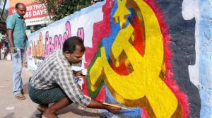 Kozhikode: CPI (M) workers paint a wall to campaign for LDF candidate ahead of assembly elections in Kozhikode on Friday. PTI Photo (PTI3_25_2016_000171A)